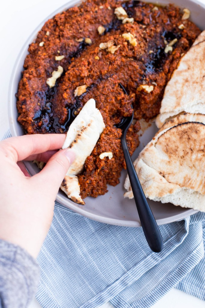 A hand dipping a slice of pita bread into the muhammara which is in a serving bowl. There is a serving spoon in the muhammara and the dip is in the same dish as some pita bread.