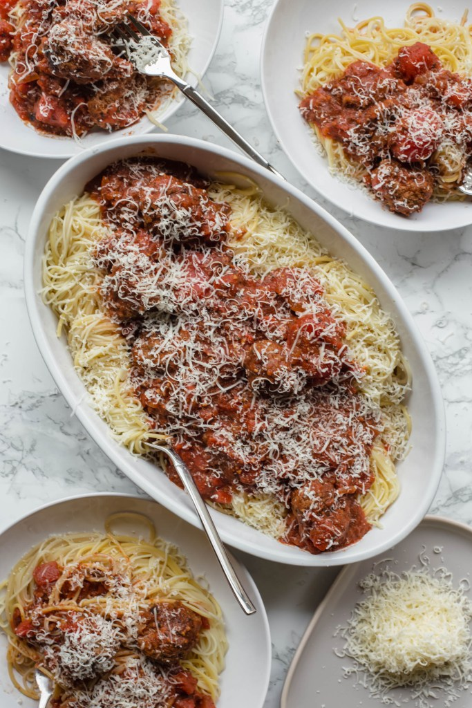 Homemade Italian meatballs and red sauce in a large bowl over spaghetti made for a large group of guests