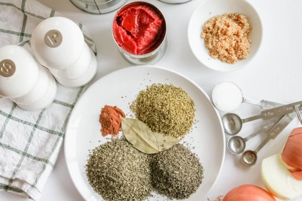 Ingredients laid out with spices on a small plate, a dish of garlic and open can of tomato paste and measuring spoons with salt in the teaspoon