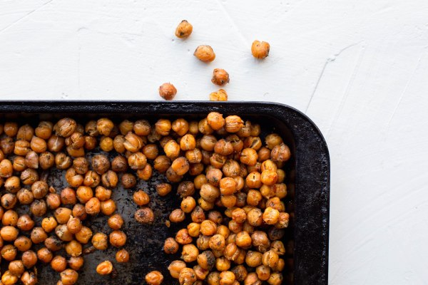Roasted chickpeas on a weathered baking sheet. A few chickpeas have fallen off the tray.