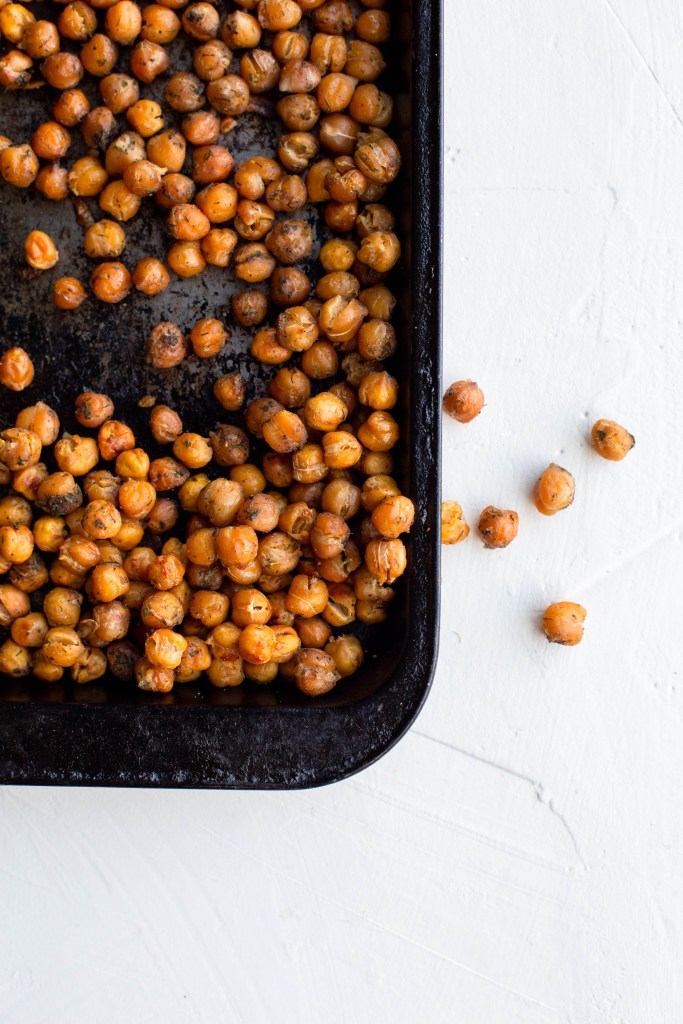 Roasted Chickpeas on an old weathered baking sheet. A few chickpeas have spilled off the side of the tray onto the white countertop