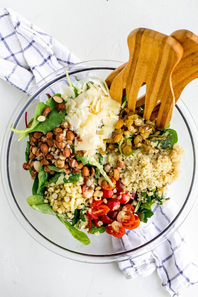 A large green salad topped with quinoa, smoked almonds, cherry tomatoes, corn, parmesan cheese and cherry tomatoes. The bowl is on top of a blue checkered napkin. There are wooden serving paddles leaning against the edge inside the bowl.