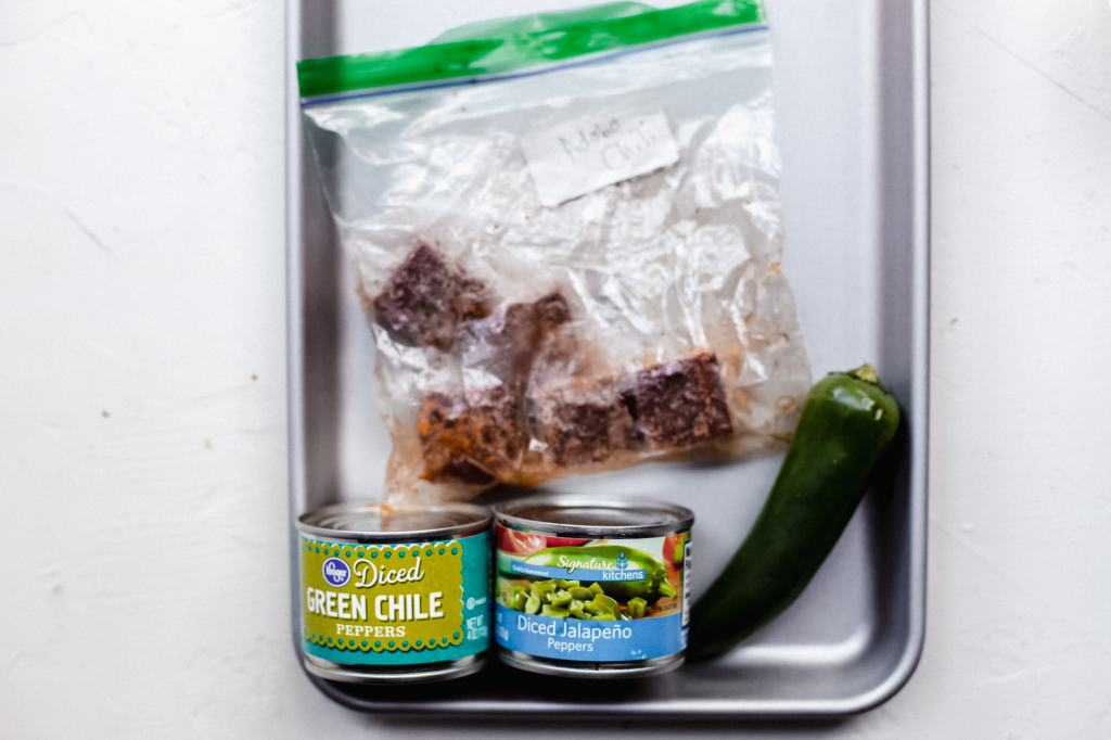 Canned jalepenos, canned diced green chilis, a fresh jalapeno and a bag of frozen adobo peppers on a sheet pan