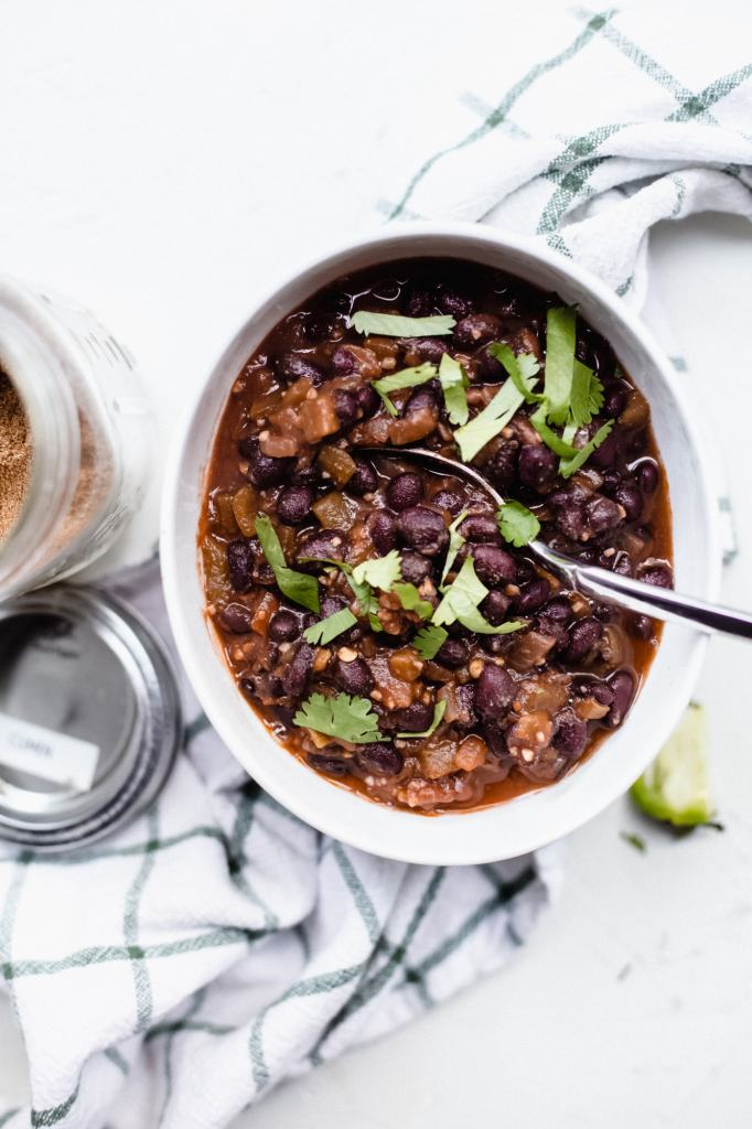 Canned black beans cooked with spices to make a mexican black bean side dish. Beans are in a bowl with a spoon on top of a decorative towel.