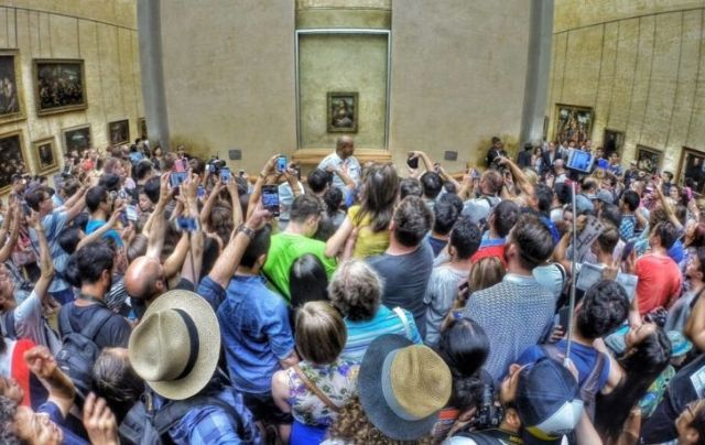 A large crowd taking pictures of Mona Lisa