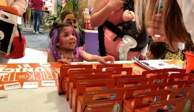 A girl being gifted a Halloween box by Unicef