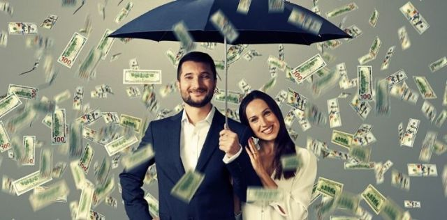 Two people under an umbrella taking cover from the raining money
