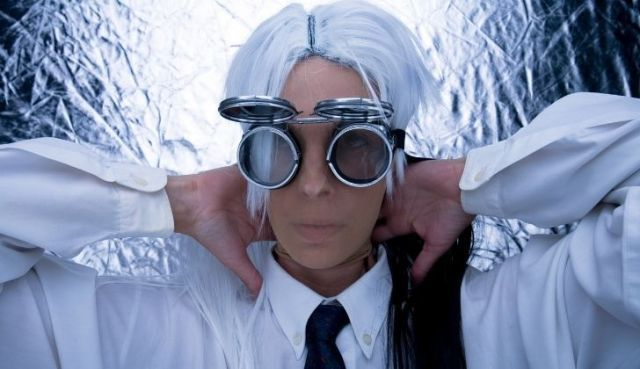 Someone wearing a futuristic costume with cool looking big circular googles and off-white/cool blue hair
