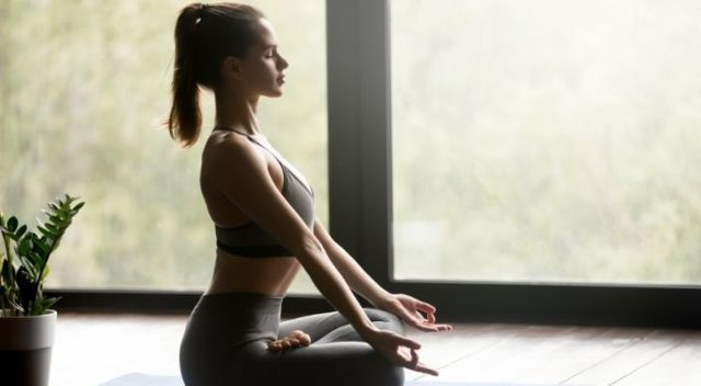 A woman sat up straight in lotus pose focussing on her breathing