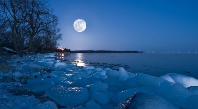 A snow moon with a snowy icy landscape on Earth