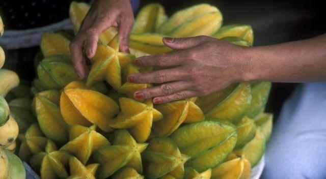 Someone handling many starfruit