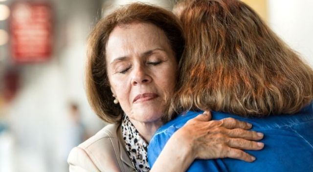 A stressed woman receiving a hug to help her feel better