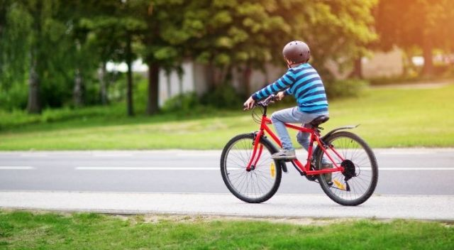 A kid riding a red bicycle