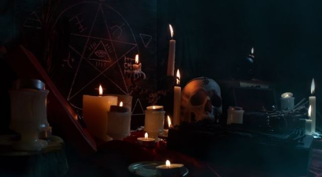 Various witchcraft items like candles and a skull