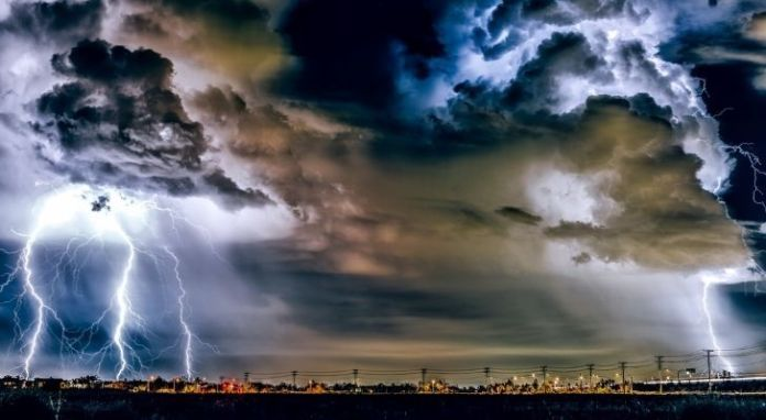 Thick heavy clouds and lightening across a city