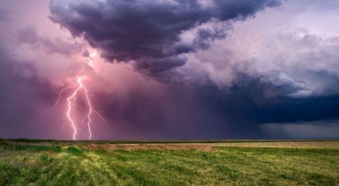 A thunderstorm across a grass field