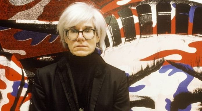 Andy Warhol with his iconic white hair and thick black framed glasses