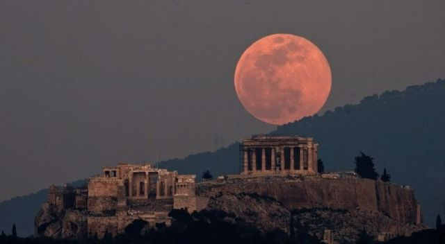 A full pink moon in the sky above ancient ruins