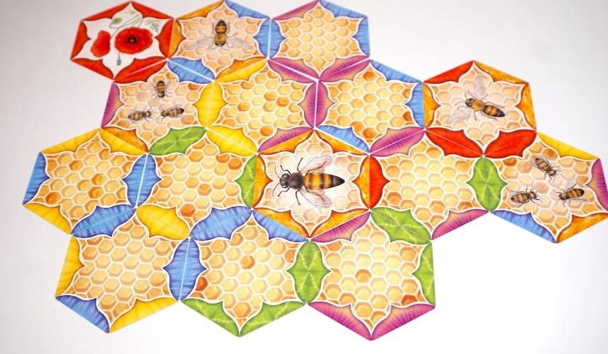 The Bears and the Bees game: Hive made of hexagon cards. Trio of bees in upper left corner, another trio of bees center right. Queen been in the center.