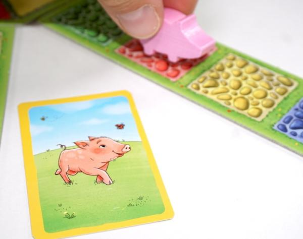 Card showing a pig, hand moving a pig