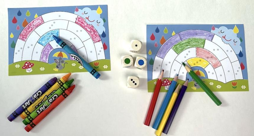 Rainbow coloring sheets with crayons and colored pencils. Dice in the middle showing blue, green, 1, 3.