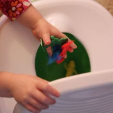 Child's hand dumping Candyland pieces into a potty