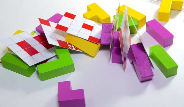 A collapsed tower of blocks and floor cards