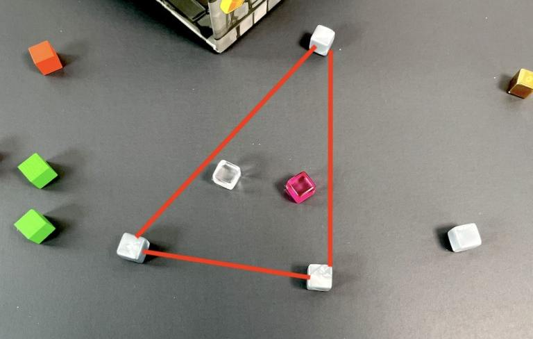 Three gray cubes with red lines overlaid to show a triangle in Dungeon Drop.