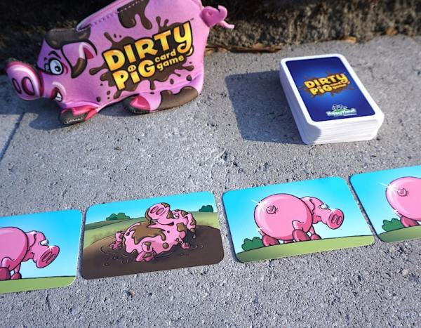 4 pig cards: 3 clean pigs and 1 muddy pig. Deck of Dirty Pig cards in background