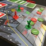 red and green figures on a board, tokens and cards visible at the edges of the picture.