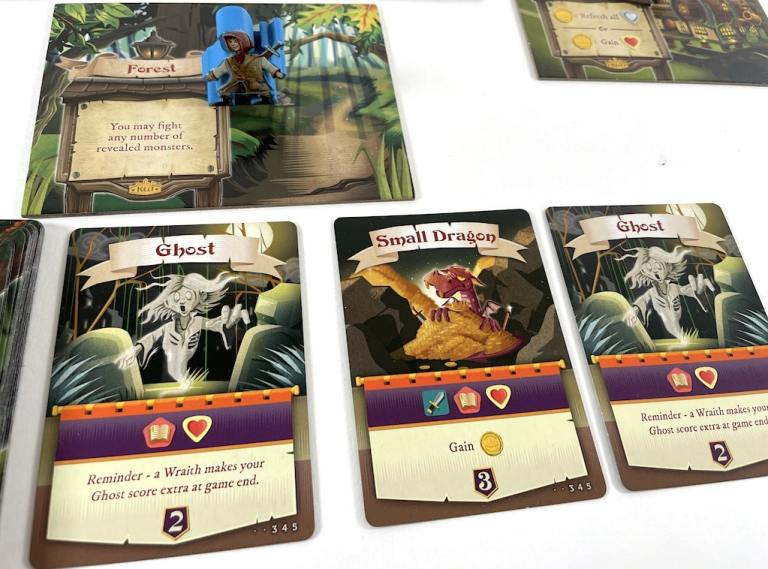 Meeple standing on Forest location. Beneath are three face-up cards: Ghost, Small Dragon, Ghost.