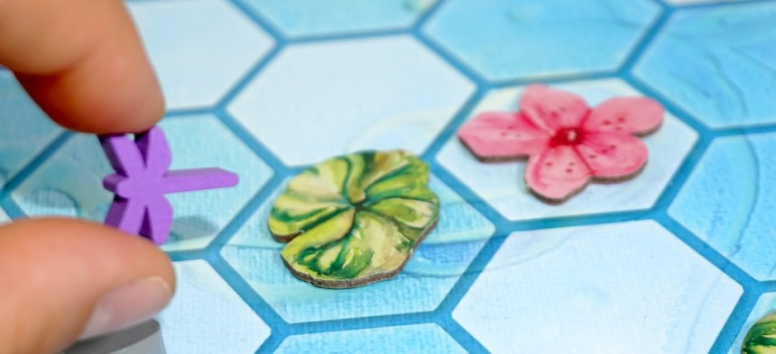 Fingers holding a dragonfly token, moving it left from a lily pad. To the right of the lily pad is a cherry blossom.