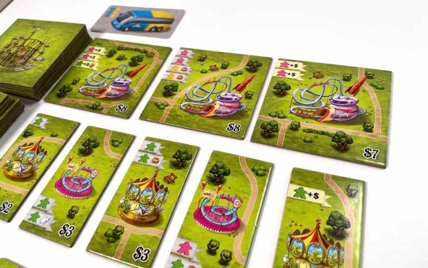 Meeple Land attraction tiles. Three large attractions with mostly pink spots; five medium attractions with mostly green spots.