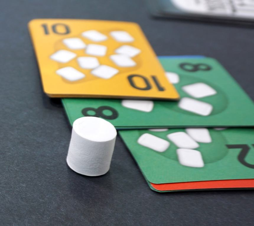 A marshmallow token next to three piles of face-up cards