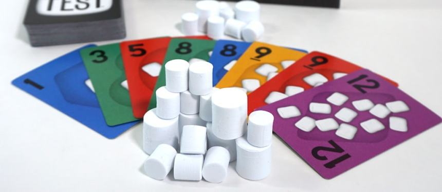 A fan of cards with marshmallow tokens stacked in front and behind.