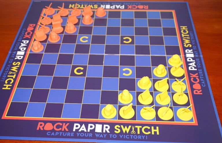 Orange and yellow players set up in opposite corners for Rock Paper Switch