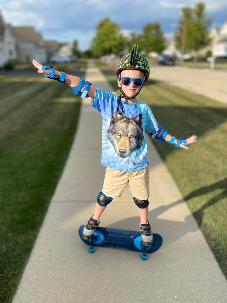 Skateboard turned on its side, boy standing on the two wheels