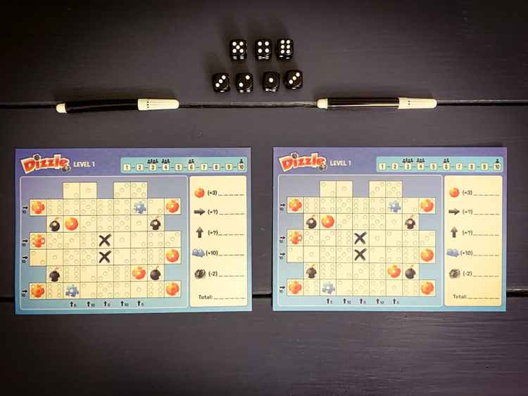 Two player sheets, two pens, seven dice