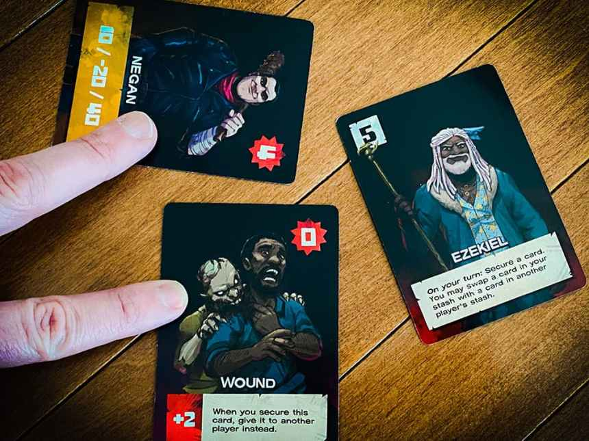 Ezekiel: Secure a card. You may swap a card in your stash with a card in another player's stash. (Swap pictured: Negan and Wound)