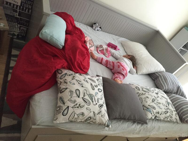 Shoshana sprawled out on a big bed