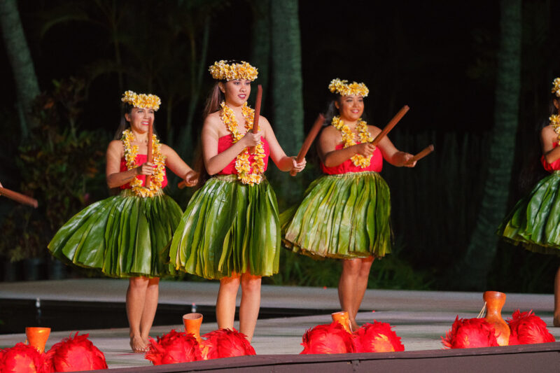 Puli dancing at Smith Family Luau on Kauai Hawaii. Three Hawaiian women wearing green palm skirts, red tops, yellow leis and yellow flower crowns.