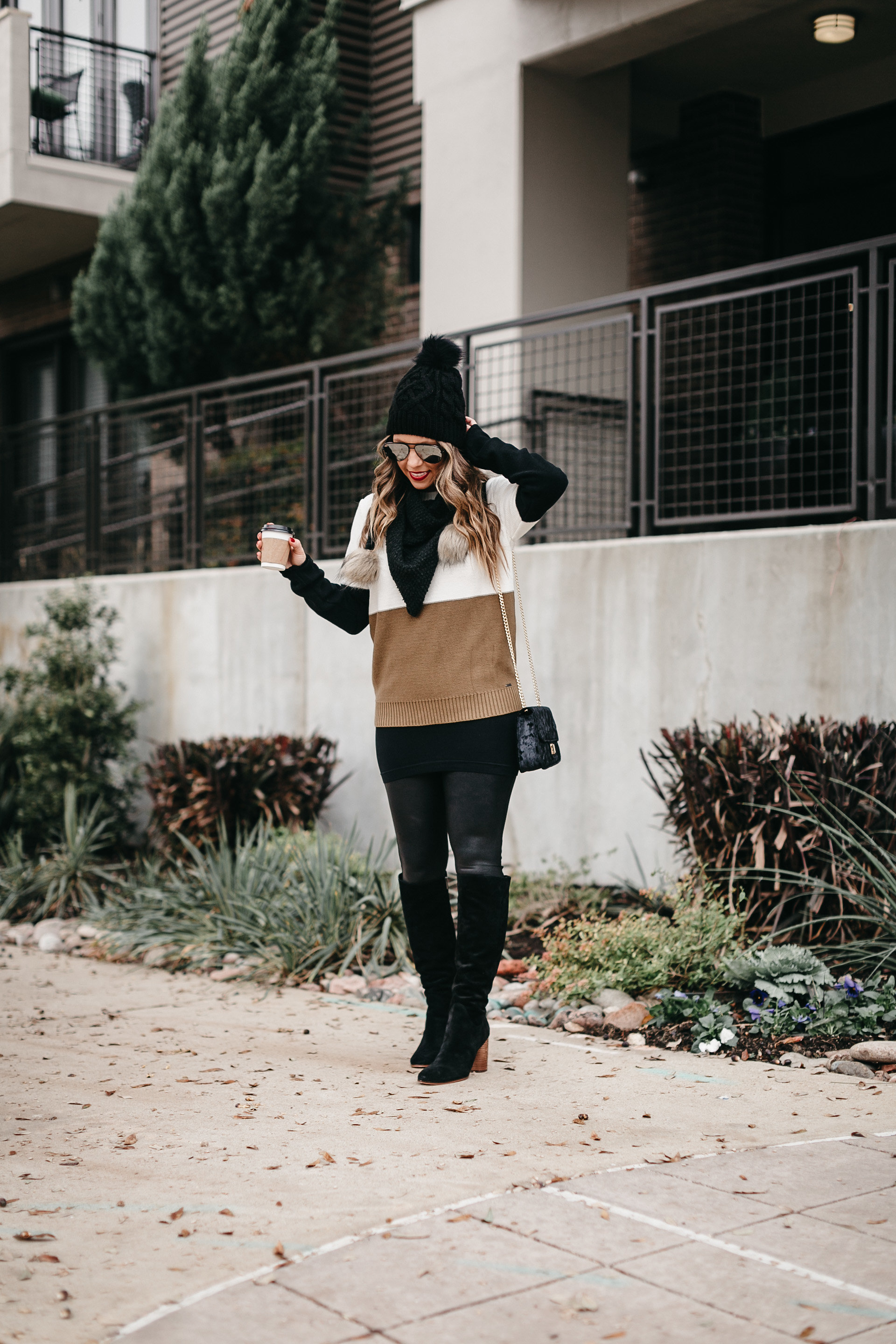 blogger with coffee wearing sweater leggings boots pom scarf pom beanie