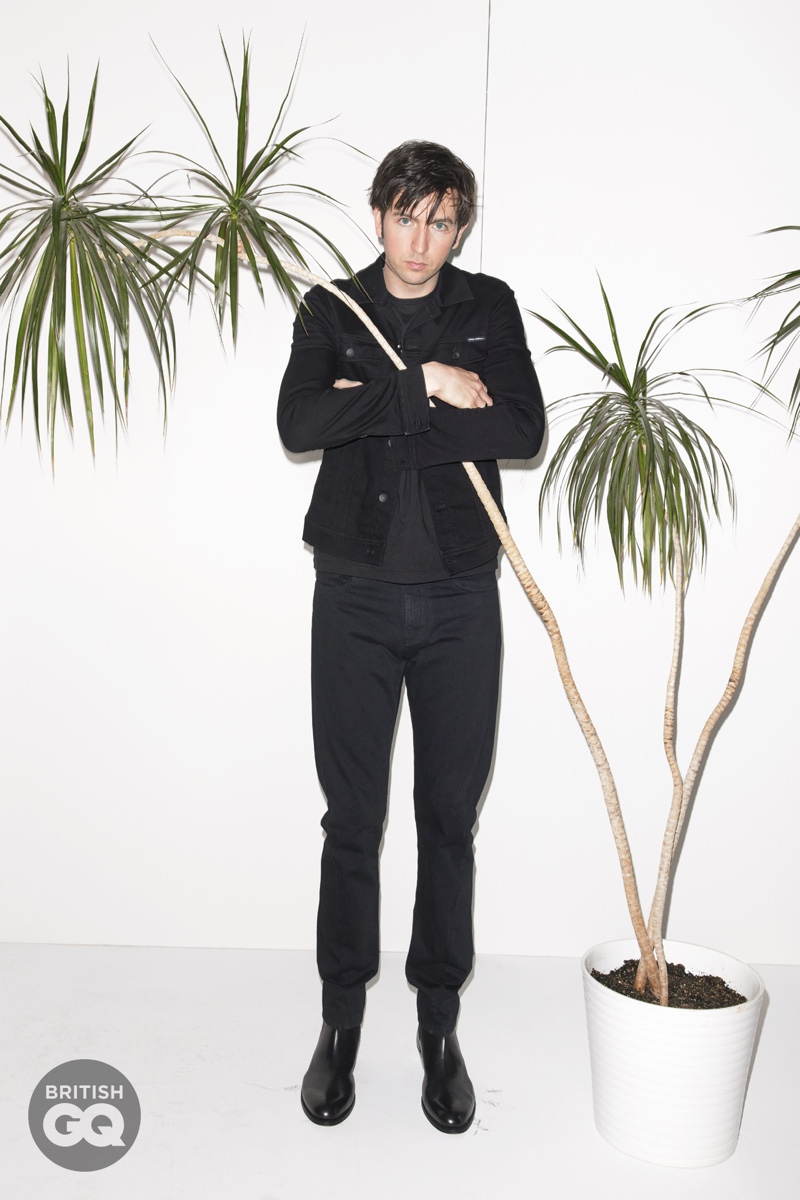 """Standing tall at 6'7"""", Nicholas Braun wears an all-black look for a British GQ photoshoot. He sports a t-shirt, jacket, and jeans from Dolce & Gabbana with Grenson boots."""