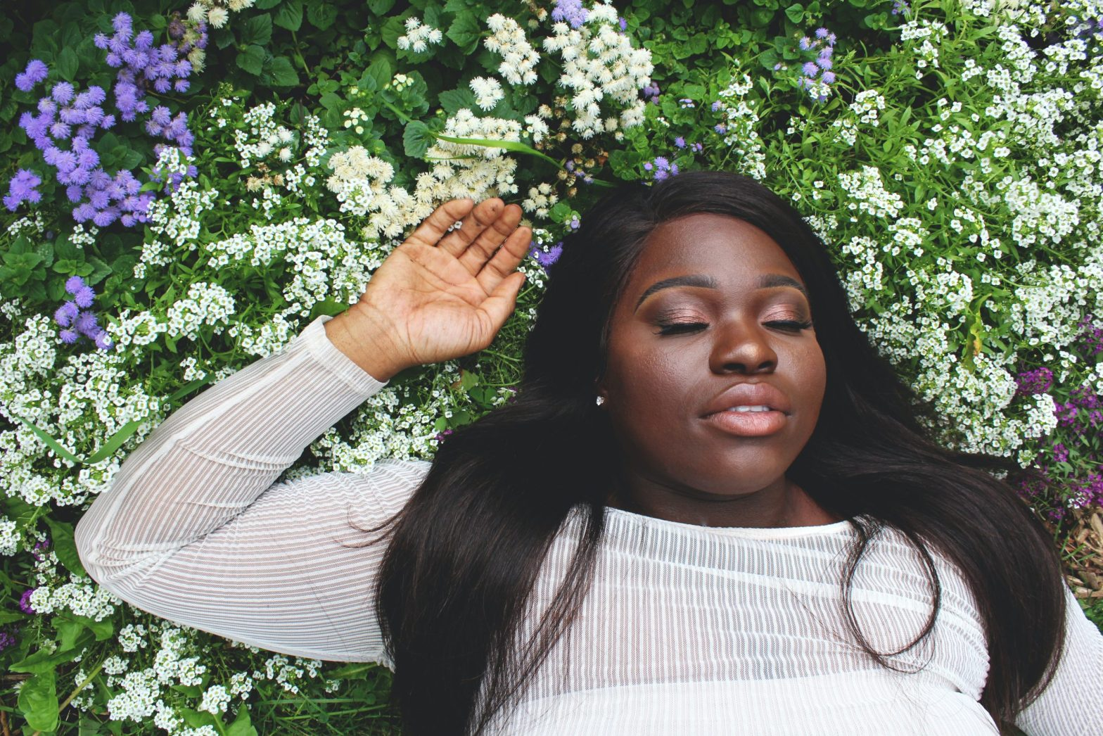 black woman lying in a bed of flowers