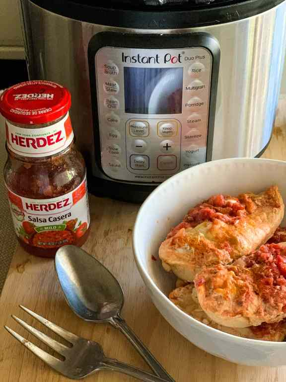 Chicken Salsa in a bowl with an Instant Pot and bottle of salsa in the background