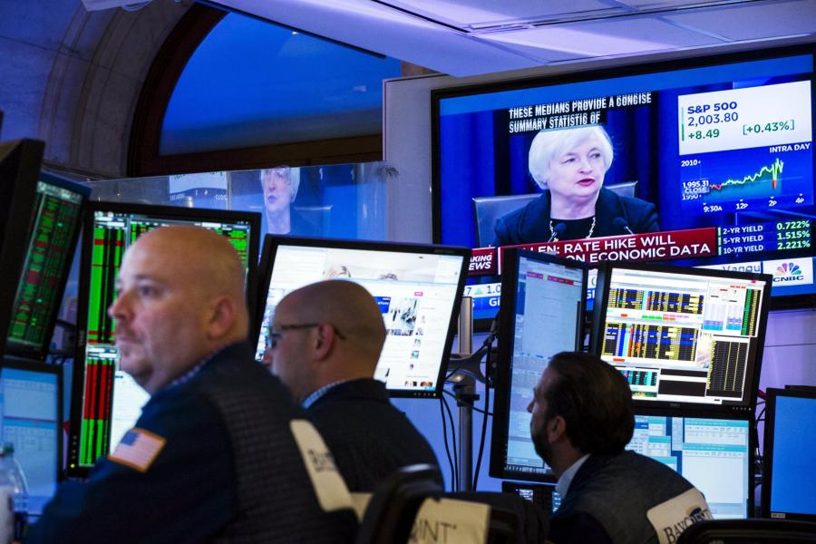 Traders-work-underneath-a-television-screen-showing-Federal-Reserve-Chair-Janet