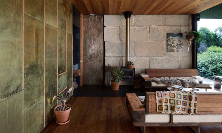 Textures of brass, concrete and wood intermingle in the house's open plan layout. Photo by Ben Hosking.