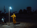 Energy property. Woman standing under light against dark night