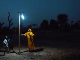 Energy property. Woman standing under light against dark night