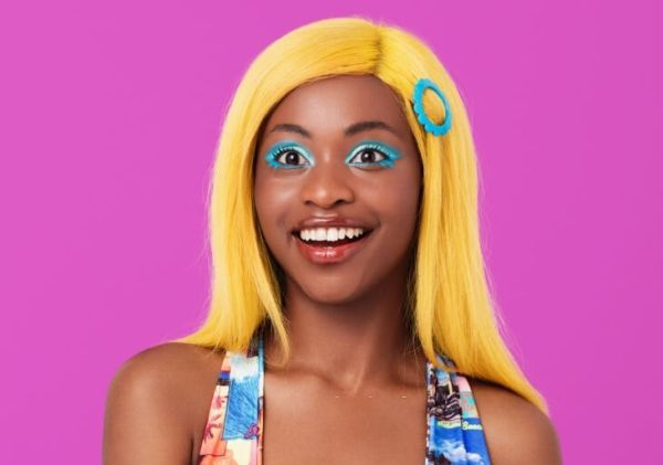 Portrait of young woman with yellow wig smiling at the camera.